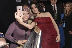 "ASSOCIATED PRESS                                 Daisy Ridley, right, takes a selfie with a fan as she arrives at the world premiere of ""Star Wars: The Rise of Skywalker"" on Monday, in Los Angeles."