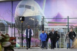 ASSOCIATED PRESS                                 Boeing workers exited the plant in front of a giant mural of a jet on the side of the manufacturing building, Monday, in Renton, Wash. Shares of Boeing fell before the opening bell on a report that the company may cut production of its troubled 737 MAX or even end production all together.