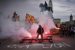 ASSOCIATED PRESS                                 A protester passes by flares during a demonstration in Lyon, central France, today.
