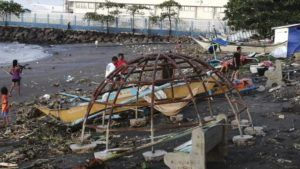 ASSOCIATED PRESS                                 Residents walks beside an outrigger and playground equipment that were damaged by Typhoon Phanfone along a coastline in Ormoc city, central Philippines. The typhoon left over a dozen dead and many homeless.