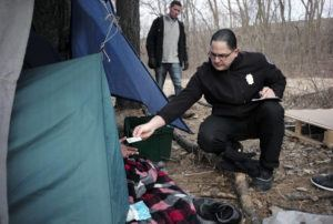 ASSOCIATED PRESS / FEB. 12 Worcester Police officer Angel Rivera, right, returns a license to an unidentified man as Rivera asks if he has been tested for Hepatitis A at the entrance to a tent where the man spent the night in a wooded area, in Worcester, Mass. At background center is Dan Cahill, City of Worcester sanitary inspector. The city was hit hard when recent hepatitis A outbreaks across the country started sickening and killing homeless people and illicit drug users.