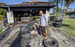 DENNIS ODA / DODA@STARADVERTISER.COM                                 Firemen investigated a garage fire this morning on Kaunoa Street in Ewa Beach. Edgardo De Jesus looked over the debris from the fire. He said he was watching TV inside his home when he smelled smoke.