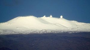 TIM WRIGHT / SPECIAL TO THE STAR-ADVERTISER                                 A blanket of snow on Mauna Kea was briefly visible early this morning from Akolea Road in Hilo. Clouds later covered the summit, obscuring the wintry scene.