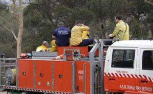 ASSOCIATED PRESS                                 Firefighters at Batemans Bay, Australia, relax after a nearby fire threat eased Saturday.