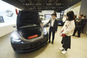 CHINATOPIX VIA ASSOCIATED PRESS                                 A saleswoman talked about a Tesla Model 3 car, Nov. 24, at a Tesla showroom in Hangzhou in eastern China's Zhejiang Province. Tesla's Shanghai factory delivered its first cars to customers Monday, and chief executive Elon Musk said the electric automaker plans to set up a design center in China to create a model for worldwide sales.