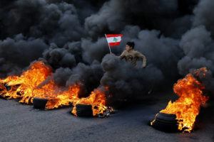 ASSOCIATED PRESS                                 An anti-government demonstrator jumps on tires that were set on fire to block a main highway as he holds a national flag, during a protest in the town of Jal el-Dib, north of Beirut, Lebanon, today. Following a brief lull, Lebanese protesters returned to the streets, blocking several roads around the capital, Beirut, and other areas of the country on Tuesday in renewed rallies against a ruling elite they say has failed to address the economy's downward spiral.
