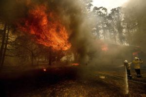 ASSOCIATED PRESS Firefighters battle the Morton Fire as it consumes a home near Bundanoon, New South Wales, Australia, Thursday.
