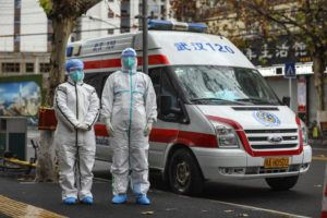 CHINATOPIX VIA AP                                 Ambulance crew members in protective gear wait for a patient outside an apartment block in Wuhan in central China's Hubei Province.
