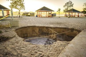 CAYMAN COMPASS VIA ASSOCIATED PRESS                                 A sinkhole is surrounded by police tape after it appeared when a powerful magnitude 7.7 earthquake struck in the Caribbean Sea between Jamaica and eastern Cuba, at Public Beach on West Bay, Grand Cayman, today.