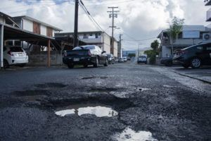 CRAIG T. KOJIMA / CKOJIMA@STARADVERTISER.COM                                 Potholes are seen on Factory Street in Kalihi in October. Cleanup of lead-contaminated soil beneath parts of Factory Street is set to begin the week of Jan. 20.