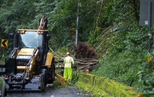 CINDY ELLEN RUSSELL / CRUSSELL@STARADVERTISER.COM                                 Crews work to clean up a mudslide in the Kailua-bound lanes of Pali Highway today.