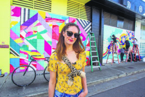 """DENNIS ODA / DODA@STARADVERTISER.COM                                 Pow! Wow! artists, including Michelle Hoogveld from Calgary, Alberta, worked on their murals Thursday in Kakaako. Hoogveld said she might title her work, pictured behind her, """"Something About Love."""""""