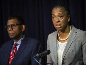 ASHLEE REZIN GARCIA/CHICAGO SUN-TIMES VIA AP                                 Dr. Terry Mason, left, chief operating officer of the Cook County Department of Public Health, looks on as Dr. Ngozi Ezike, right, director of the Illinois Department of Public Health, discusses the second confirmed case of a new virus in Illinois during a press conference at the Thompson Center, Thursday, in Chicago. Health officials are reporting the first U.S. case of person-to-person spread of the new virus from China. The latest patient is the husband of the Chicago woman who got sick after she returned from a trip to China.