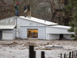 BEN LONERGAN/EAST OREGONIAN VIA AP Nate Fuller and Archie Morrow await rescue on the roof of a home in Thorn Hollow outside of Adams, Ore. The pair were stranded when they attempted to rescue the elderly couple who were stuck in the house as waters from the Umatilla River began to rise. All were rescued by helicopter that evening. Severe flooding in eastern Oregon closed a major freeway on Friday, forced evacuations in low-lying areas and stranded at least one family on their roof as other parts of the Pacific Northwest also braced for more flooding and landslides.