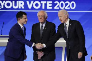 ASSOCIATED PRESS                                 From left, Democratic presidential candidates former South Bend Mayor Pete Buttigieg, shakes hands with former Vice President Joe Biden as Sen. Bernie Sanders, I-Vt., watches Friday.