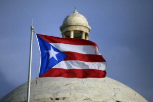 ASSOCIATED PRESS / 2015 The Puerto Rican flag flies in front of Puerto Rico's Capitol as in San Juan, Puerto Rico. A senior Puerto Ricon official said that the island's government has lost more than $2.6 million after falling for an email phishing scam.