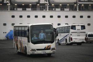 ASSOCIATED PRESS A bus leaves the quarantined Diamond Princess cruise ship at a port Sunday in Yokohama, near Tokyo.