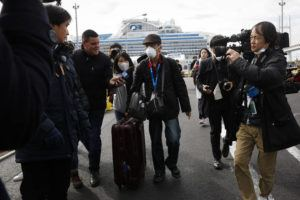 ASSOCIATED PRESS                                 An unidentified passenger was surrounded by the media after he disembarked from the quarantined Diamond Princess cruise ship, Wednesday, in Yokohama, near Tokyo. Passengers tested negative for COVID-19 started disembarking Wednesday.