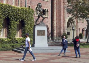 ASSOCIATED PRESS                                 People pose for photos in front of the iconic Tommy Trojan statue on the campus of the University of Southern California in Los Angeles. USC will phase in free tuition for students from families with an annual income of $80,000 or less.