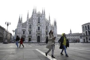 ASSOCIATED PRESS                                 A woman wearing a sanitary mask walks past the Duomo gothic cathedral in Milan, Italy, today. A dozen Italian towns saw daily life disrupted after the deaths of two people infected with the virus from China and a pair of case clusters without direct links to the outbreak abroad. A rapid spike in infections prompted authorities in the northern Lombardy and Veneto regions to close schools, businesses and restaurants and to cancel sporting events and Masses.