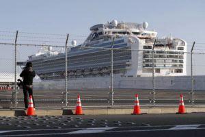 ASSOCIATED PRESS                                 A photographer takes photos near the quarantined Diamond Princess cruise ship anchored at a port in Yokohama, near Tokyo, on Friday.