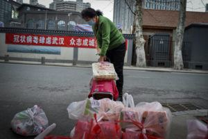 "ASSOCIATED PRESS                                 A woman uses a trolley bag to collect foods distributed by volunteers outside her home in Wuhan in central China's Hubei province on Saturday. South Korea and China both reported a rise in new virus cases as the South Korean prime minister warned that the fast-spreading outbreak linked to a local church and a hospital in the country's southeast had entered a ""more grave stage."""