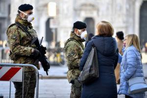 CLAUDIO FURLAN/LAPRESSE VIA ASSOCIATED PRESS                                 Italian soldiers wearing sanitary masks patrolled Duomo square in downtown Milan, Italy, Monday. At least 190 people in Italy's north have tested positive for the COVID-19 virus and four people have died, including an 84-year-old man who died overnight in Bergamo, the Lombardy regional government reported.