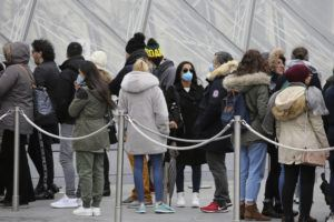 ASSOCIATED PRESS Tourists, some wearing a mask, queue to enter the Louvre museum in Paris. The world is scrambling to get on top of the new coronavirus outbreak that has spread from its epicenter in China to most corners of the planet. Governments and doctors are presenting an array of approaches as the virus disrupts daily routines, business plans and international travel around the world.
