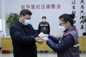 XINHUA VIA AP                                 Chinese President Xi Jinping, left, wearing a protective face mask, receives a temperature check at a community health center in Beijing on Monday.