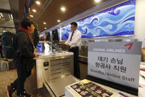 STAR-ADVERTISER / 2013                                 Passengers check in at Asiana Airlines in Honolulu. Asiana is the latest carrier to cut back on its Hawaii service in the wake of the coronavirus.