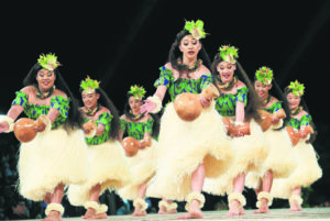 JAMM AQUINO / 2019                                 The women of Halau Ka Lei Mokihana o Leinaʻala, of Kalaheo, Kauai, perform during the hula 'auana competition in the 56th annual Merrie Monarch Festival. This year's festival has been canceled over coronavirus concerns.