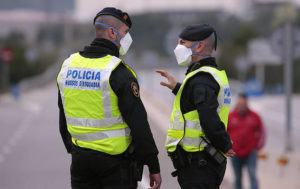 ASSOCIATED PRESS                                 Police officers stood on the closed-off road near Igualada, Spain, today. Over 60,000 people awoke today in four towns near Barcelona confined to their homes and with police blocking roads.