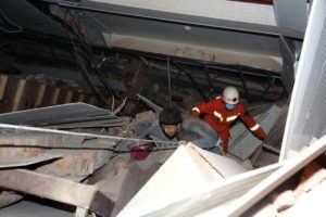 CHINATOPIX VIA AP                                 A man is assisted out from the rubble of a collapsed hotel building in Quanzhou city in southeast China's Fujian province. The hotel used for medical observation of people who had contact with coronavirus patients collapsed in southeastern China on Saturday, trapping dozens, state media reported.
