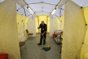 ASSOCIATED PRESS                                 Steve Moody, director of nursing at Central Maine Medical Center, mopped the floor of a tent outside the emergency entrance to the hospital where patients are tested for of the coronavirus, today, in Lewiston, Maine. U.S. hospitals are setting up circus-like triage tents, calling doctors out of retirement, guarding their supplies of face masks and making plans to cancel elective surgery as they brace for an expected onslaught of coronavirus patients.