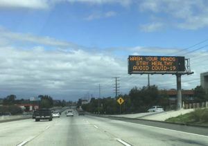 """ASSOCIATED PRESS A Caltrans freeway sign reads: """"Wash your hands, Stay healthy, Avoid COVID-19"""" in the San Fernando Valley section of Los Angeles."""