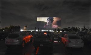 """ASSOCIATED PRESS                                 Viewers in parked cars watch the animated film """"Onward"""" at the Paramount Drive-In Theatres on Thursday in Paramount, Calif. The drive-in theater, long a dwindling nostalgia act in a multiplex world, is experiencing a momentary return to prominence."""