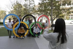 ASSOCIATED PRESS A group of students from Uruguay pose for a souvenir picture on the Olympic Rings set outside the Olympic Stadium in Tokyo on March 21.