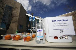 ASSOCIATED PRESS                                 A bottle of hand sanitizer stands next to free lunches for people under the age of 18 outside the Aurora Public Library as branch manager Phillip Challis, back, looks on in an effort to help city residents and reduce the spread of the new coronavirus today.