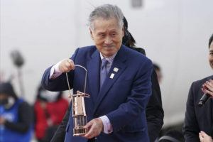 ASSOCIATED PRESS                                 Tokyo 2020 Olympics chief Yoshiro Mori carries the Olympic flame during the flame arrival ceremony at Japan Air Self-Defense Force Matsushima Base in Higashimatsushima in Miyagi Prefecture, Japan, on March 20.