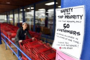 Social distancing guidelines are displayed outside the Trader Joe's grocery story in Annapolis, Md., Wednesday, March 25, 2020, as Jessica Izumi moves carts. (AP Photo/Susan Walsh)