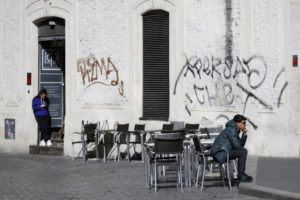 LAPRESSE VIA AP                                 A man sits at a table as others are empty at a cafe in Largo Argentina square in Rome.