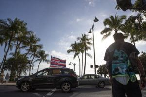 CINDY ELLEN RUSSELL / CRUSSELL@STARADVERTISER.COM                                 Participants in the convoy drive along Kalakaua Avenue in Waikiki.