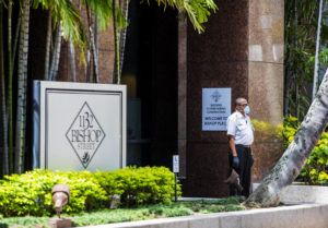 DENNIS ODA / DODA@STARADVERTISER.COM Tenants of the 1132 Bishop St. office building were notified of a worker's positive coronavirus case. A security guard stands outside the building.