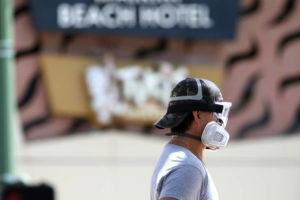 ASSOCIATED PRESS                                 A man wears goggles and a mask as he walks a dog along Waikiki Beach on Saturday.