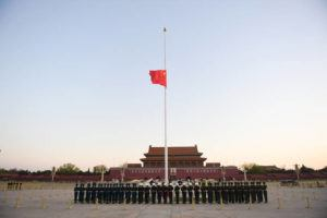 In this photo released by China's Xinhua News Agency, an honor guard stands in formation as a Chinese national flag flies at half-staff at Tiananmen Square in Beijing, Saturday, April 4, 2020. China plans to pause for 3 minutes of nationwide mourning on Saturday in rememberance of those who have died in the coronavirus outbreak. (Ju Huanzong/Xinhua via AP)