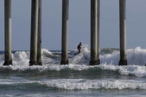 A surfer rides a wave in Huntington Beach, Calif., Saturday, April 4, 2020. With beaches shut down across California as authorities try to stem the spread of the coronavirus, some surfers are simply watching the waves break at home on their TVs. A few are still surfing, seeking out-of-the way breaks or areas where sunbathers are banned from the sand but those carrying boards are tolerated as long as they stay at least six feet apart in the water. (AP Photo/Chris Carlson)