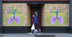 ASSOCIATED PRESS                                 A pedestrian wearing a mask walked past paintings featuring lungs and a tree by Burgandy Viscosi on the boarded-up Re-Bar nightclub and theatre, today, in downtown Seattle.
