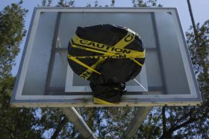ASSOCIATED PRESS                                 Yellow caution tape and a plastic tarp covered a basketball rim at McKinley Park in Sacramento, Calif., Tuesday. The park remains open but the rims were covered because people were not following social distancing rules in place due to the coronavirus outbreak.