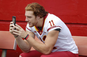 ASSOCIATED PRESS                                 Iowa State tight end Chase Allen takes a photo with his cell phone during Iowa State's annual NCAA college football media day in Ames, Iowa, in 2018. While autograph-signing and public appearances have been traditional ways athletes could make extra money, opportunities now are tied to social media posts where athletes could in the future be paid for posting sponsored content.