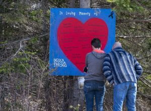 ASSOCIATED PRESS                                 People paid their respects at a roadside memorial in Portapique, Nova Scotia, on Sunday.